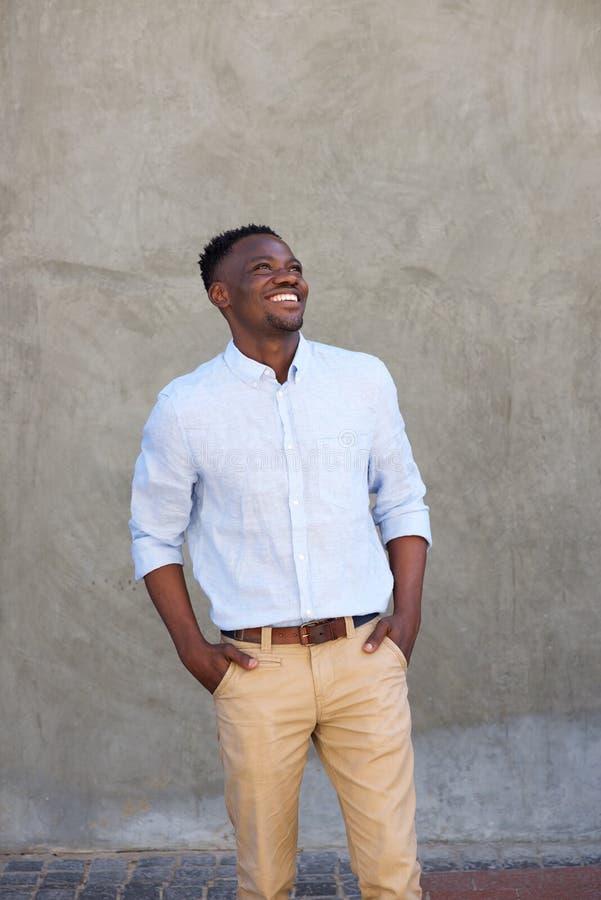 Homem negro novo moderno que sorri com mãos em uns bolsos fotografia de stock