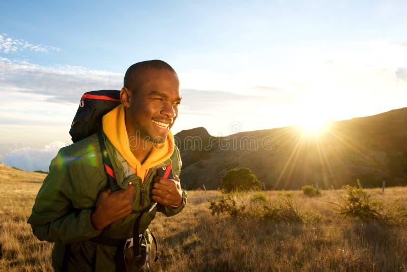 Homem negro novo que anda com a trouxa nas montanhas com nascer do sol no fundo foto de stock