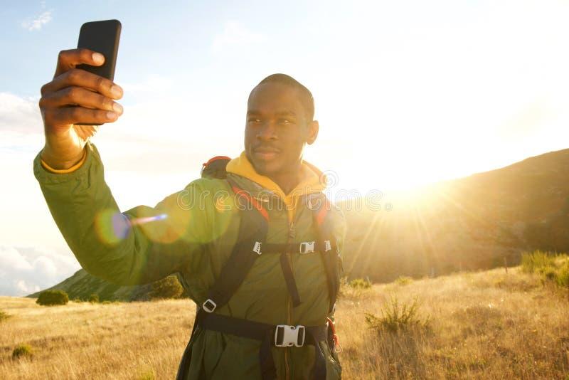 Homem negro novo que caminha nas montanhas que tomam o selfie com telefone celular e por do sol no fundo foto de stock