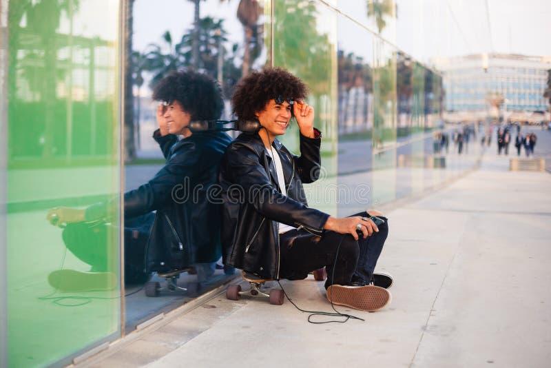Homem negro novo que senta-se com móbil e fones de ouvido na cidade ensolarada imagem de stock royalty free