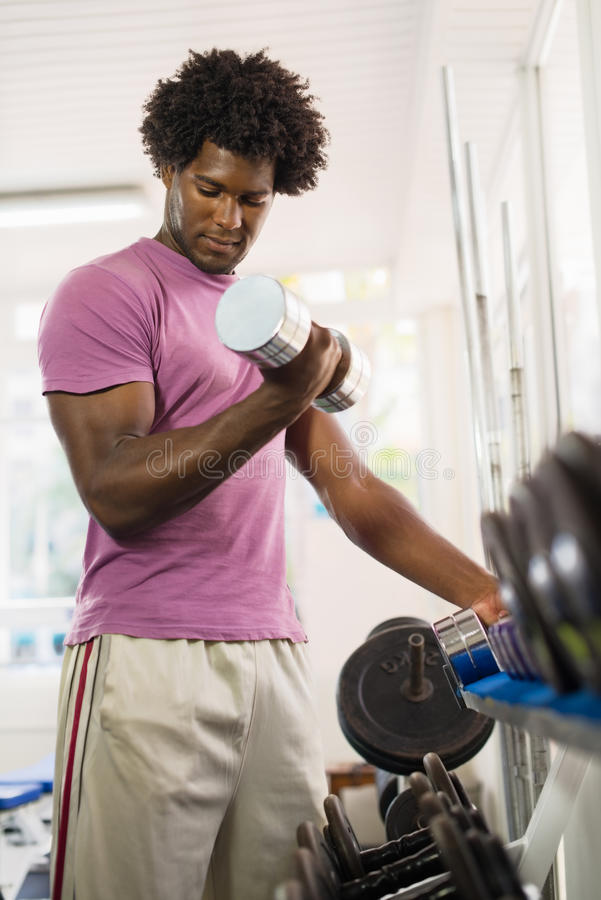 Homem negro novo que toma pesos da cremalheira na ginástica foto de stock