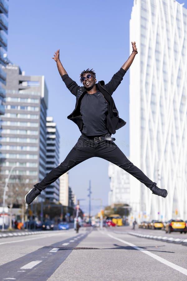 Homem negro novo que veste a roupa ocasional que salta no fundo urbano Conceito do estilo de vida Óculos de sol vestindo do indiv imagem de stock