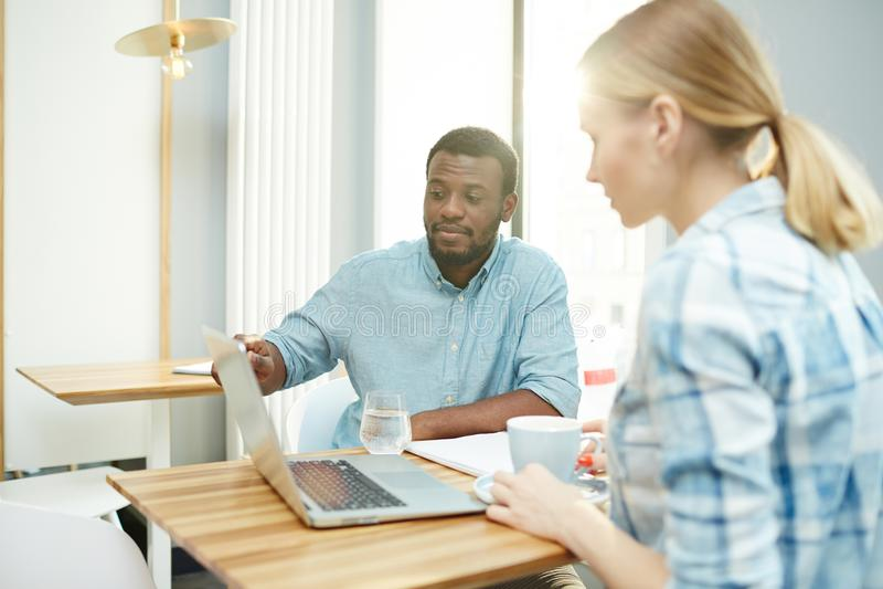 Homem negro que aponta no portátil para o colega fotos de stock royalty free