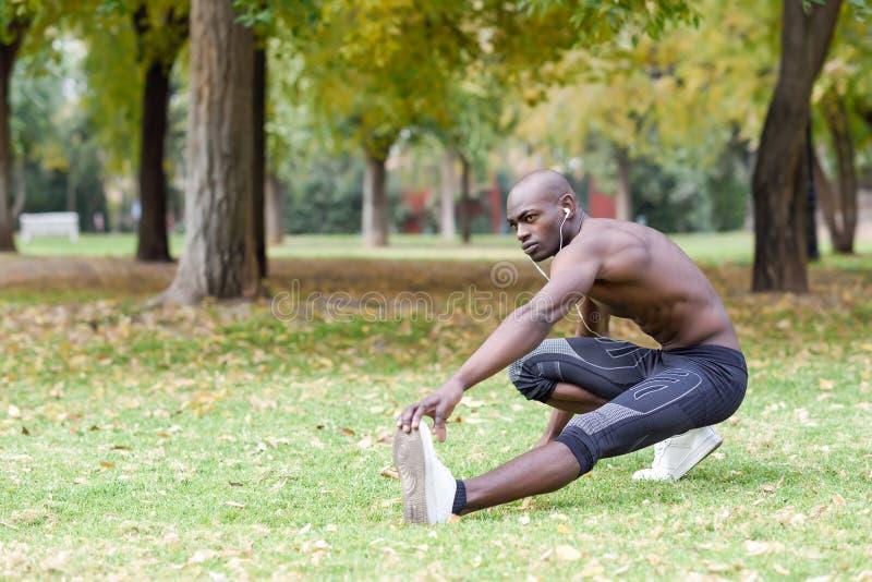 Homem negro que faz o esticão antes de correr no fundo urbano foto de stock royalty free