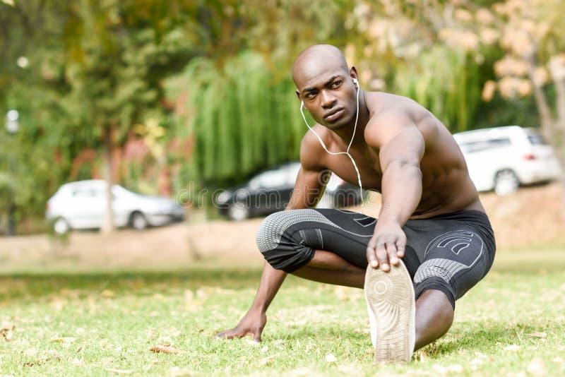 Homem negro que faz o esticão antes de correr no fundo urbano imagens de stock