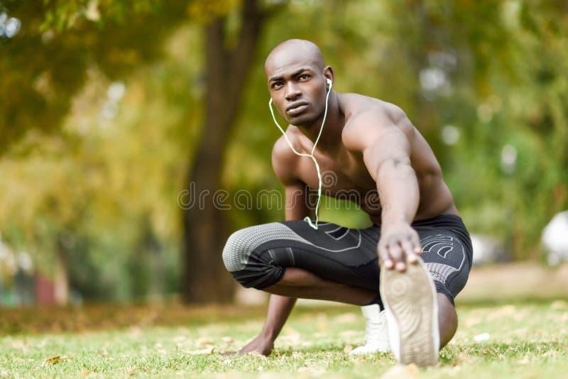 Homem negro que faz o esticão antes de correr no fundo urbano foto de stock
