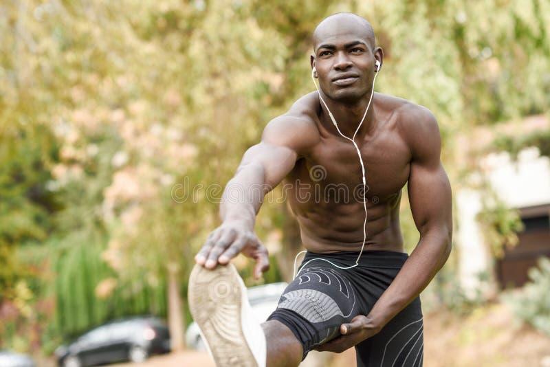 Homem negro que faz o esticão antes de correr no fundo urbano imagem de stock royalty free