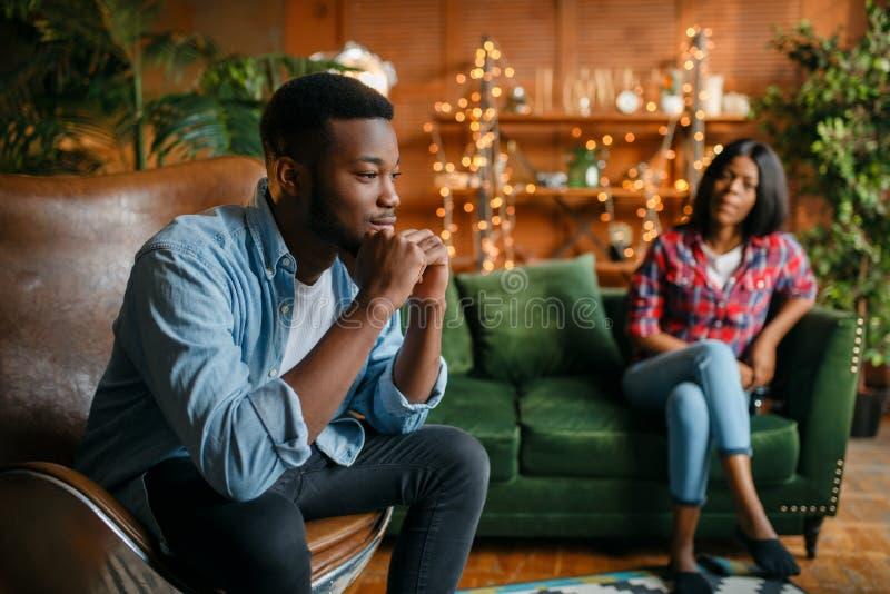 Homem negro que senta-se em uma cadeira contra sua mulher imagens de stock royalty free