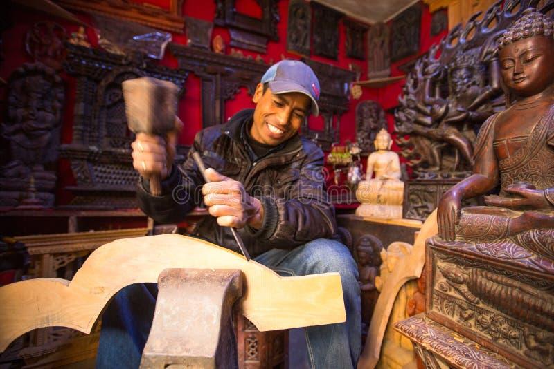 Homem nepalês não identificado que trabalha em sua oficina de madeira, o 19 de dezembro de 2013 em Bhaktapur, Nepal fotografia de stock