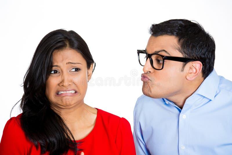 Homem Nerdy que tenta beijar a mulher esnobe foto de stock
