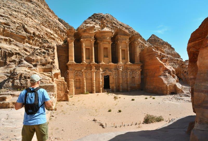 Homem no anúncio Deir o templo do monastério em PETRA em Jordânia foto de stock