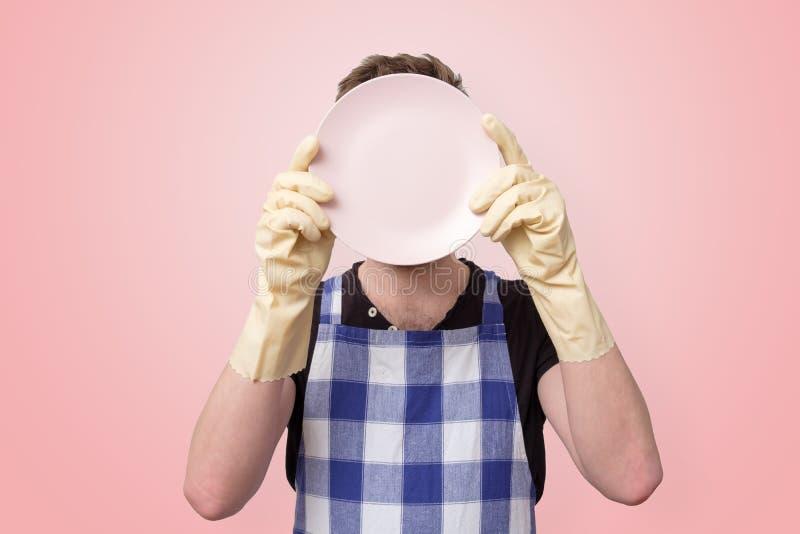Homem no avental e nas luvas de borracha que guardam a placa limpa foto de stock