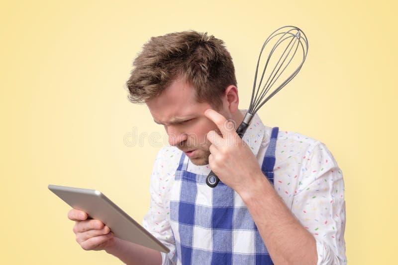 Homem no avental que procura a receita no Internet foto de stock