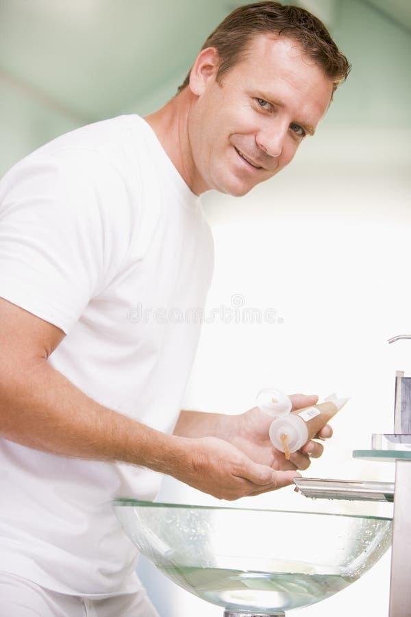 Homem no banheiro com gel de cabelo imagem de stock