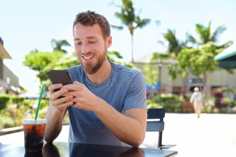 Homem no café usando o envio de mensagem de texto esperto do app do telefone foto de stock