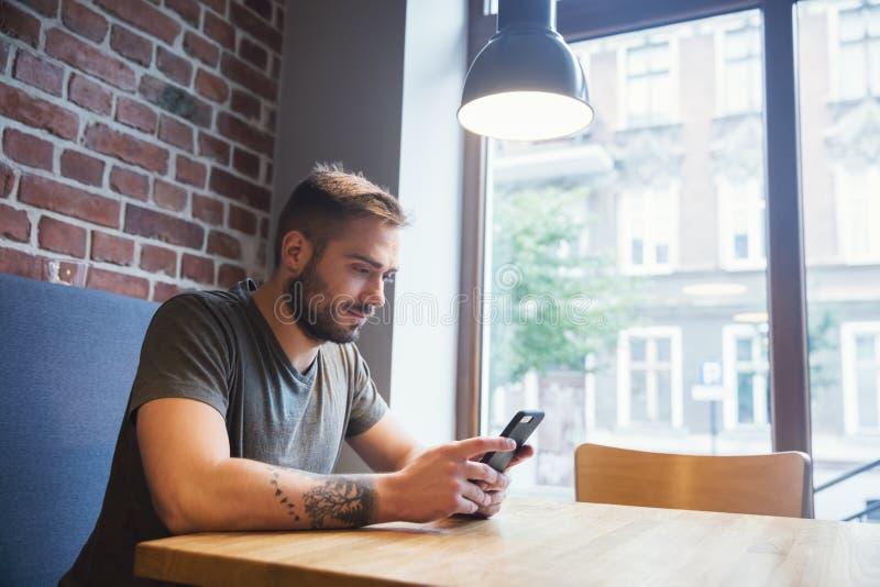Homem no café usando seu telefone celular fotografia de stock