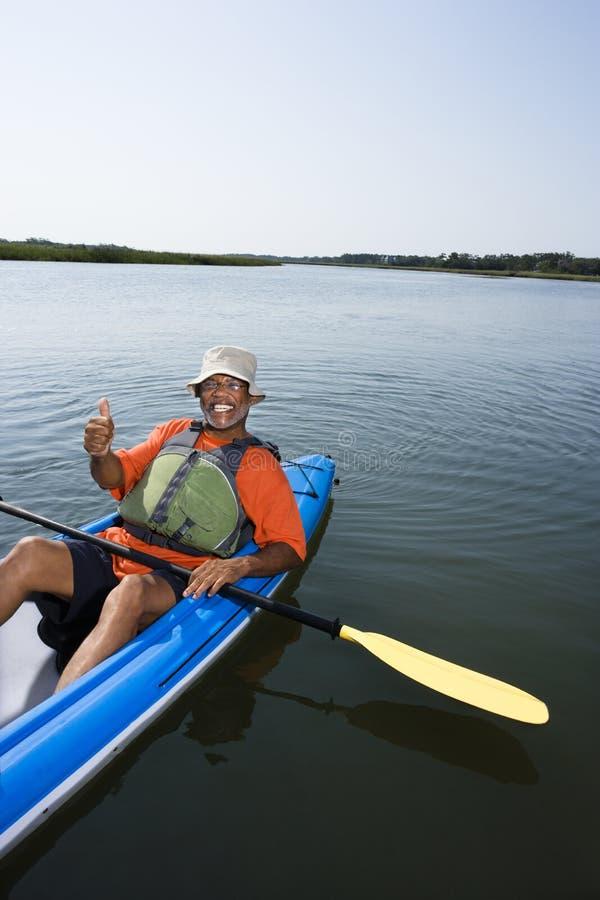Homem no caiaque. imagem de stock