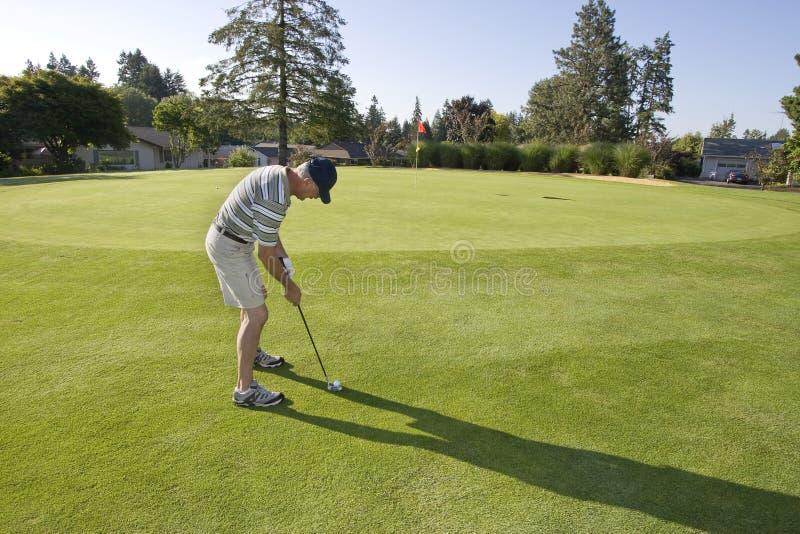 Homem no campo de golfe fotografia de stock