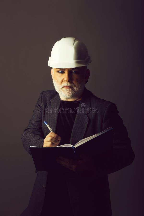 Homem no capacete de segurança com caderno fotografia de stock royalty free