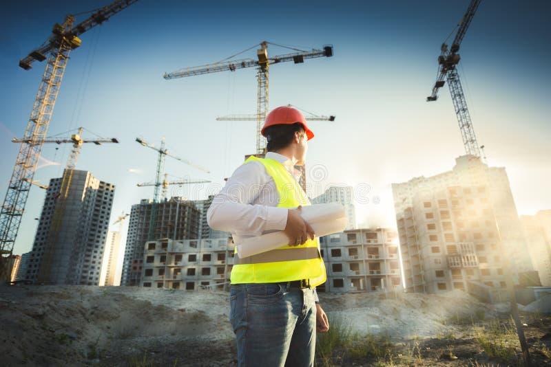 Homem no capacete de segurança e no revestimento verde que levantam no terreno de construção foto de stock