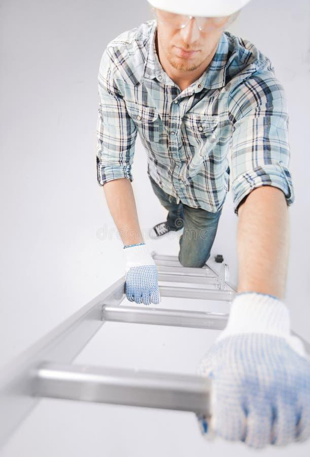 Homem no capacete e luvas que escalam a escada fotografia de stock royalty free