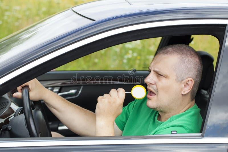 Homem no carro com pirulito amarelo foto de stock royalty free