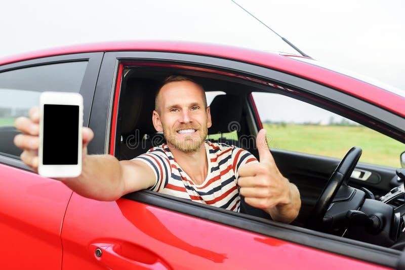Homem no carro que mostra o telefone esperto foto de stock