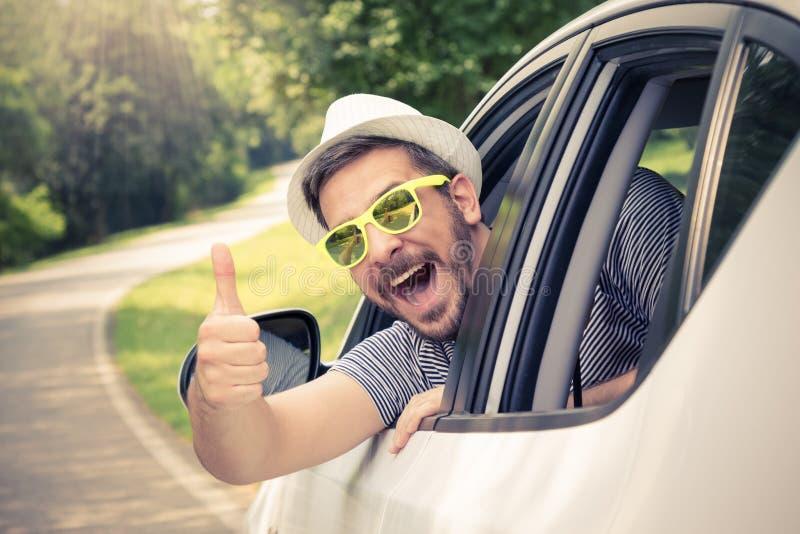 Homem no carro que mostra os polegares acima fotografia de stock
