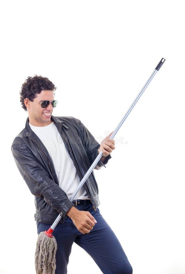 Homem no casaco de cabedal que joga em uma vassoura imagem de stock
