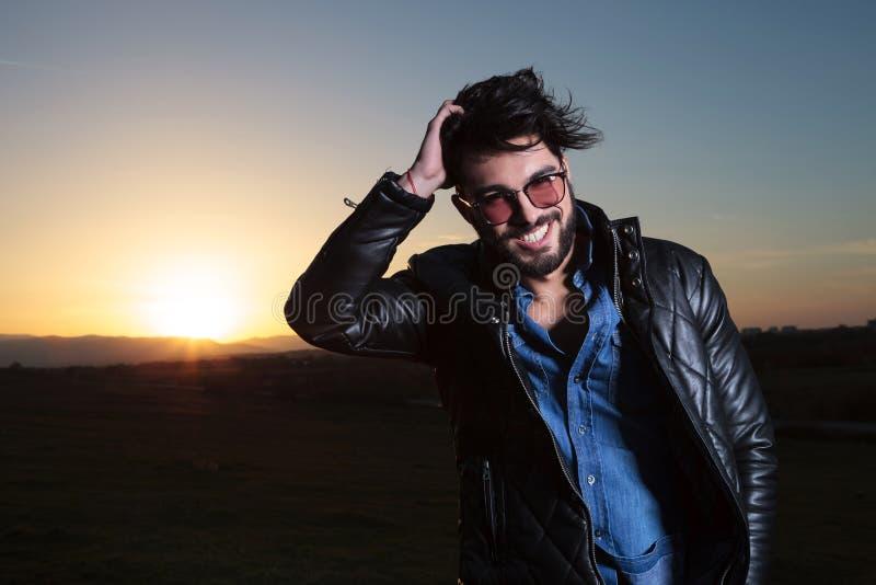 Homem no casaco de cabedal que passa sua mão com o seu imagens de stock