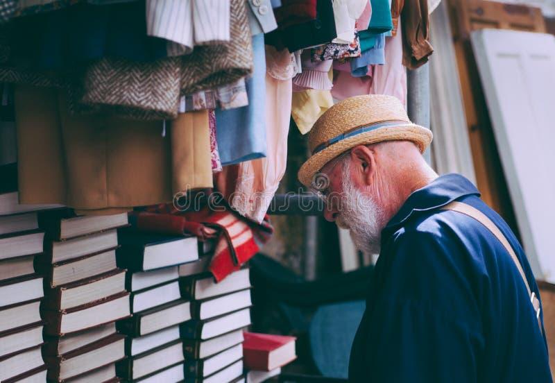 Homem no chapéu de Brown Sun que enfrenta livros empilhados cobertos pretos fotos de stock royalty free