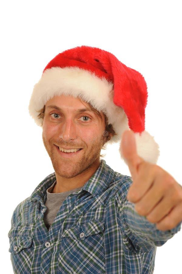 Homem no chapéu de Santa com polegar acima imagens de stock royalty free