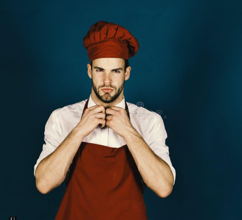 Homem no chapéu e no avental do cozinheiro de Borgonha O cozinheiro trabalha na cozinha Culinária e conceito de cozimento profiss foto de stock