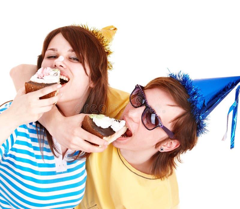 Homem no chapéu e na menina do partido que comem o bolo. fotografia de stock royalty free