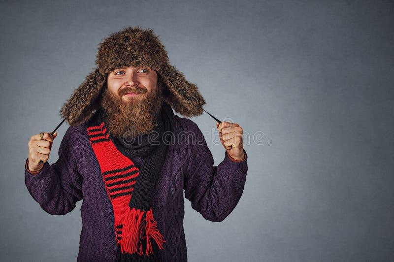 Homem no chapéu forrado a pele, no scraf vermelho e na camiseta roxa escura olhando para tomar partido sonhando acordado fotos de stock