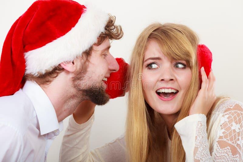 Homem no chap?u de Santa que sussurra ? orelha da mulher fotografia de stock