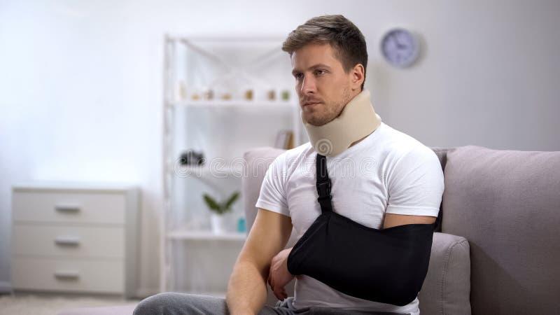 Homem no colar cervical da espuma e no estilingue do braço infelizes devido à inabilidade, reabilitação fotografia de stock