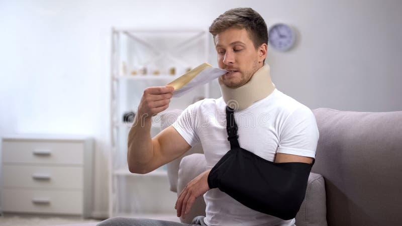 Homem no colar cervical da espuma e no estilingue do braço que tentam receber a letra do envelope fotos de stock