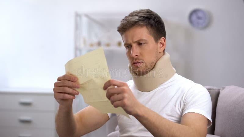 Homem no colar cervical da espuma que lê a conta médica chocada com preço alto, saúde fotografia de stock
