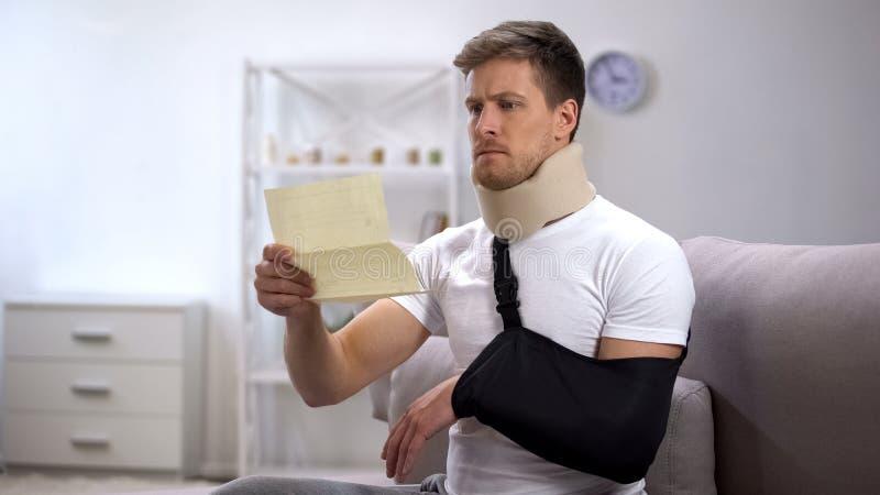 Homem no colar da espuma e no estilingue cervicais do braço que lê a conta médica, preço chocante fotos de stock royalty free