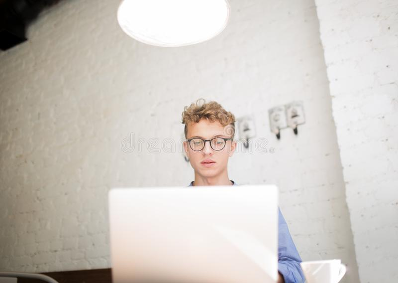 Homem no desenvolvimento bem sucedido dos vidros de projetos digitais usando o rede-livro portátil foto de stock