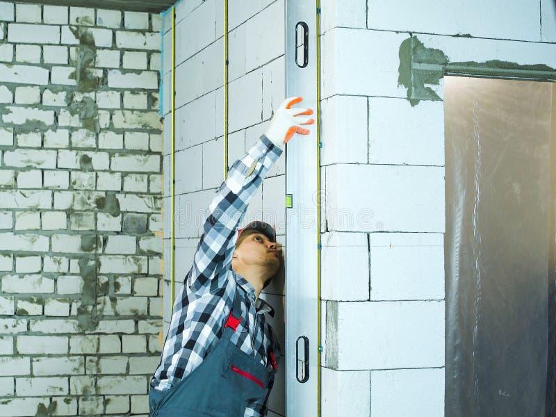 Homem no desgaste do trabalho que pressiona o nível de bolha para obstruir verticalmente a parede fotografia de stock