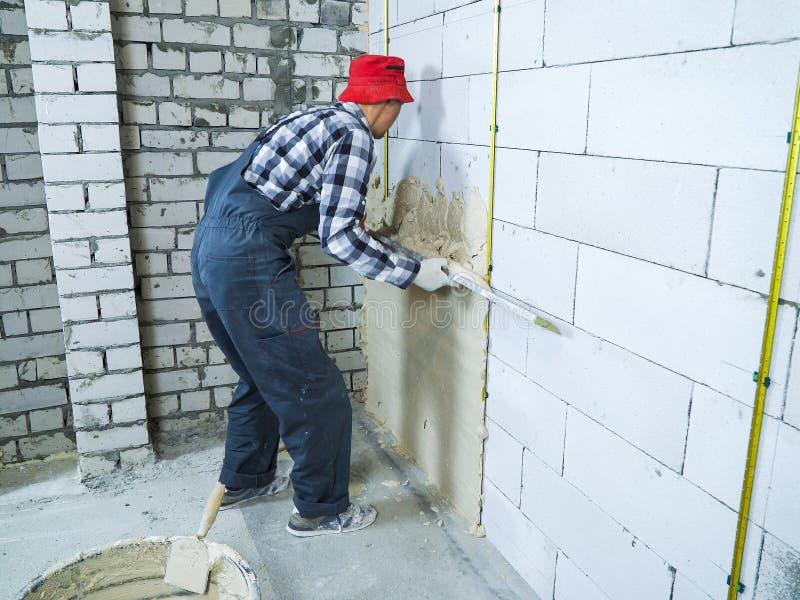 Homem no emplastro de espalhamento do desgaste do trabalho na parede do bloco com régua da construção fotografia de stock royalty free