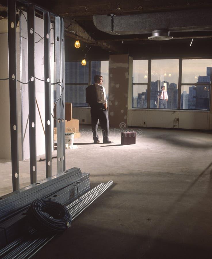 Homem no escritório da construção nova fotografia de stock royalty free