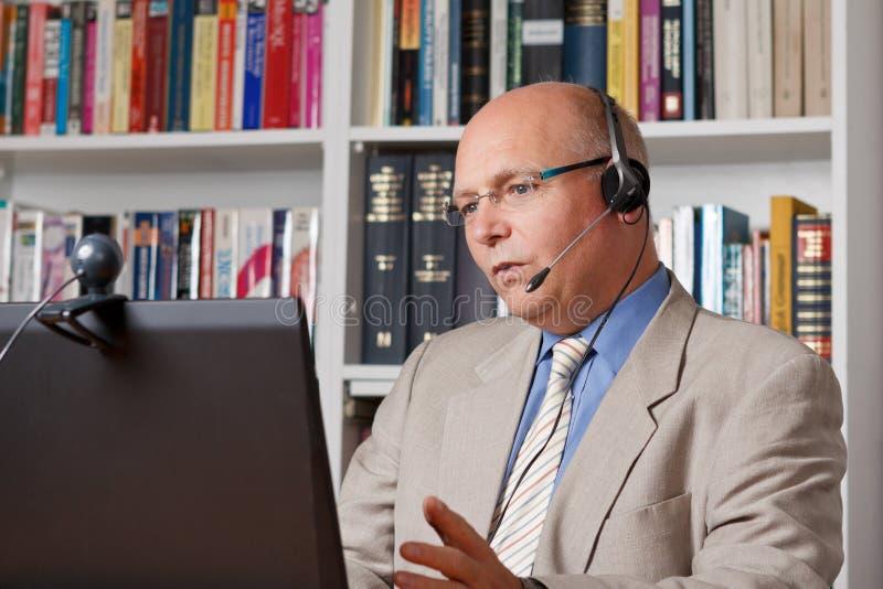 Homem no escritório domiciliário que fala através do Internet foto de stock