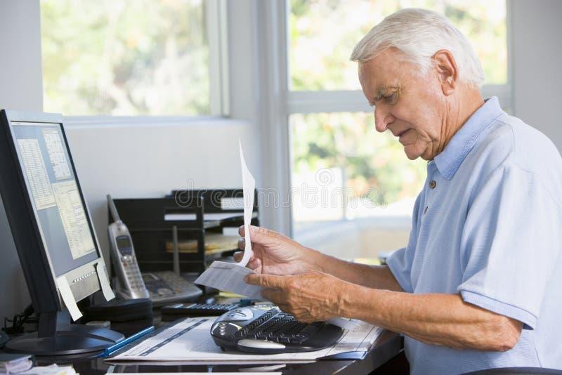 Homem no escritório home com documento e computador foto de stock royalty free