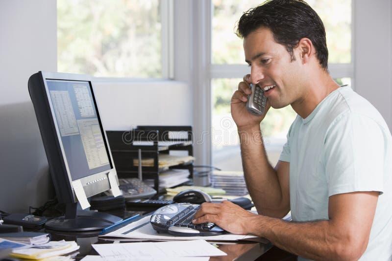 Homem no escritório home no telefone usando o computador fotos de stock royalty free
