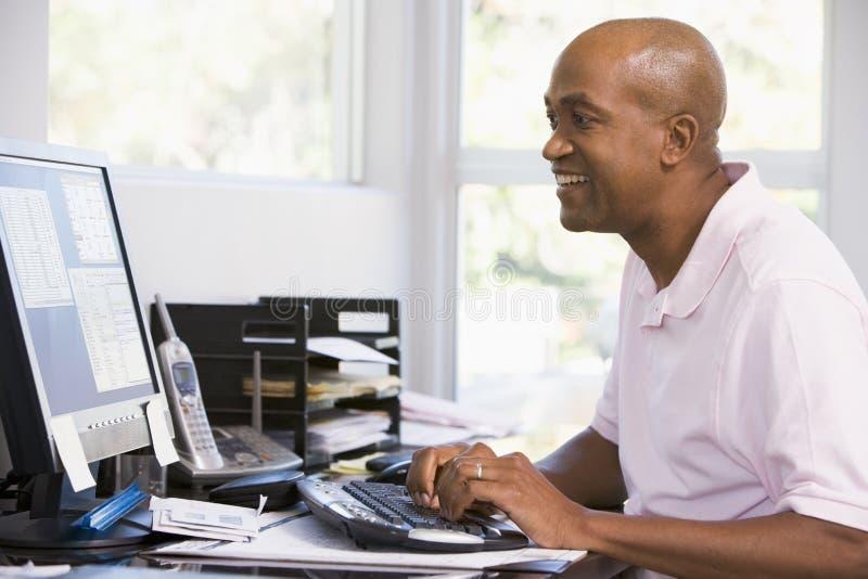 Homem no escritório home usando o computador e o sorriso fotografia de stock royalty free
