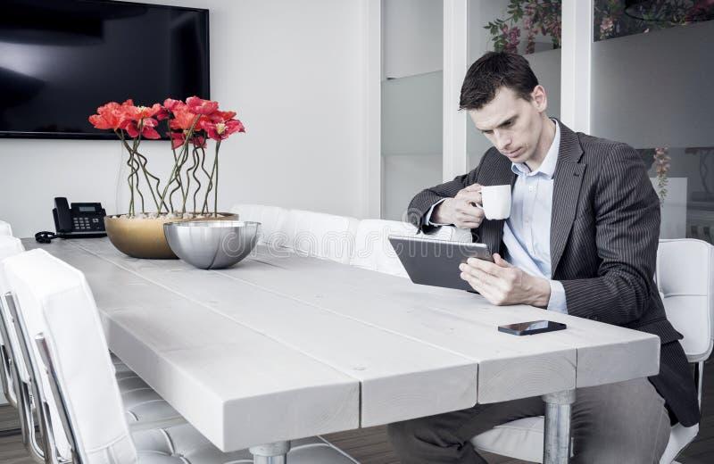 Homem no escritório usando o PC da tabuleta fotos de stock