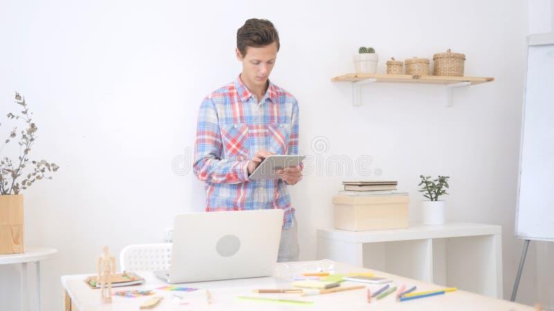 Homem no escritório usando a tabuleta eletrônica, desenhista criativo, agência fotografia de stock royalty free